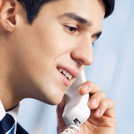 Young businessman or call center worker with phone Banque d'images - 115400884