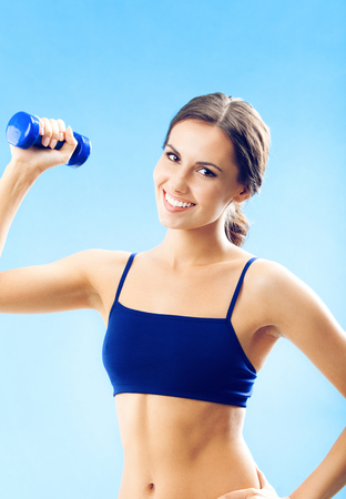 Portrait of young woman in fitness wear exercising with dumbbell, over blue background Banque d'images - 115400887