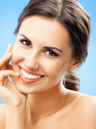 Portrait of beautiful young happy smiling woman, over blue background Banque d'images - 115400891