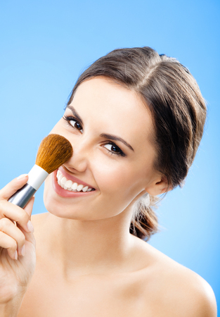Happy smiling woman with cosmetics brush, against blue background Banque d'images - 115400998