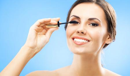 Jeune femme souriante avec pinceau cosmétique, sur fond bleu