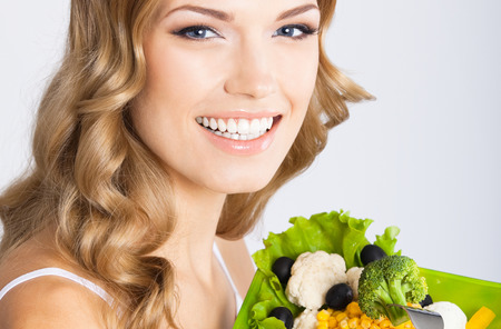 Cheerful young beautiful woman with healthy vegetarian salad, over grey background Banque d'images - 115401007