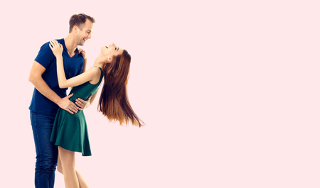 Hugging or dancing couple, looking at each other, with copyspace empty area for slogan or advertising text message, over pink background. Caucasian models in love, relationship, dating, flirting, lovers, romantic studio concept.