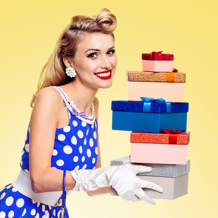 Happy woman in pin-up style blue dress in polka dot and white gloves, holding gift boxes, on yellow background. Caucasian blond model in retro fashion and vintage concept.