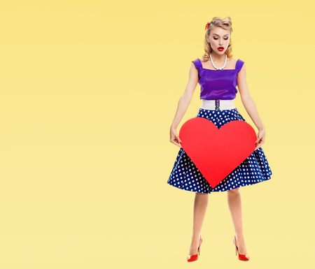 Full body of woman holding red heart symbol, dressed in pin-up style dress with polka dot, with copyspace area for slogan or advertising text message, on yellow background. Caucasian blond model in retro fashion and vintage concept.