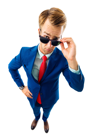 Are you seriously?! Full body portrait of funny skeptic young businessman in blue confident suit and red tie, looking through sunglasses, top angle view shot, isolated against white background. Business concept.