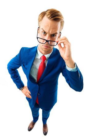 Are you seriously?! Full body portrait of funny skeptic young businessman in blue confident suit and red tie, looking through glasses, top angle view shot, isolated against white background. Business concept. Stockfoto