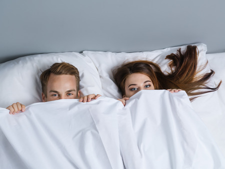 Young attractive playfull couple peeping from bedsheet on the bed at bedroom. Caucasian models in love, relationship, dating, happy people, bedtime concept shot. 写真素材