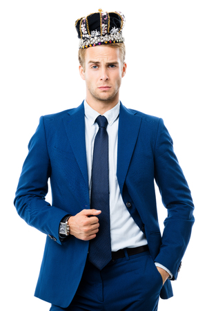 I am business king! Portrait of young serious businessman in crown, isolated on white background. Leadership and business success concept.
