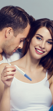 Beautiful young amorous couple, finding out results of a pregnancy test. Caucasian white models - in love, relationship, dating, happy lovers, concept shot, against grey background. Vertical banner composition.