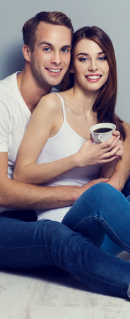 Portrait of young smiling couple with cup of coffee, sitting on floor, close to each other and looking at camera. Caucasian models in love, relationship, dating, happy lovers, concept shot. Vertical banner composition.