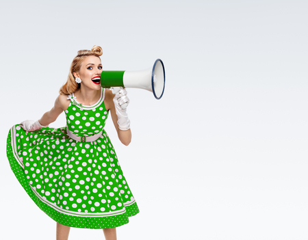 Portrait of woman holding megaphone, dressed in pin-up style green dress in polka dot and white gloves, on grey background. Caucasian blond model posing in retro fashion vintage studio shoot.