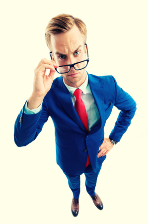 Are you seriously?! Full body portrait of funny skeptic young businessman in blue confident suit and red tie, looking through glasses, top angle view shot, isolated over yellow background. Business concept.