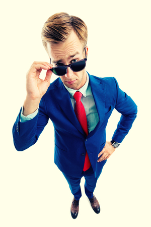 Are you seriously?! Full body portrait of funny skeptic young businessman in blue confident suit and red tie, looking through sunglasses, top angle view shot, isolated over yellow background. Business concept. Stockfoto
