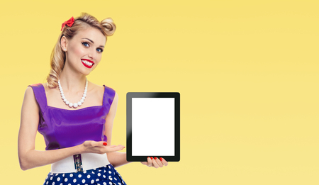Woman, showing blank no-name tablet pc monitor, dressed in pin-up style dress in polka dot, with copy space area for some slogan or advertising text message, on yellow background. Retro, vintage concept.