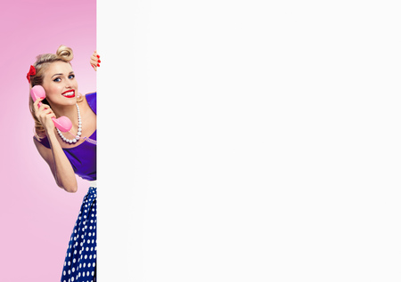woman with phone, in pin-up style dress, showing blank signboard with copyspace area, on pink background. Caucasian blond model posing in retro fashion and vintage concept studio shoot.