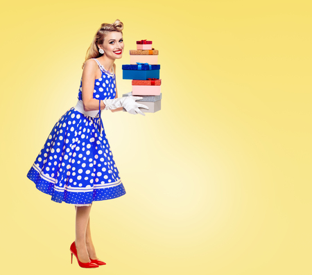 Full body of happy woman in pin-up style blue dress in polka dot and white gloves, holding gift boxes, with copy space area for some slogan or advertising text message, on yellow background. Retro, vintage concept. Imagens