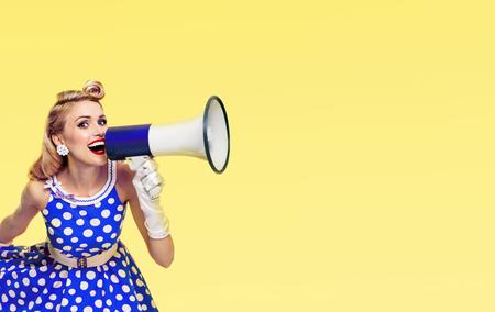 Retrato de mujer sosteniendo megáfono, vestida con un vestido azul estilo pin up con lunares y guantes blancos, con área de espacio de copia para algún lema o mensaje de texto publicitario, sobre fondo amarillo. Concepto retro, vintage.