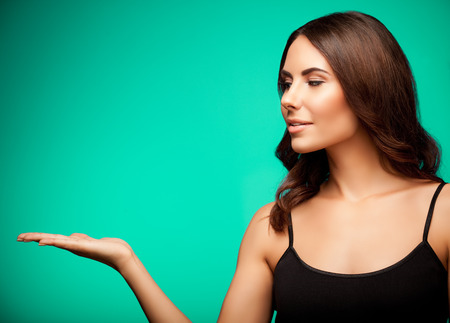 Portrait of smiling young woman in black casual clothing, showing something or blank copyspace area for slogan or text message, on green background