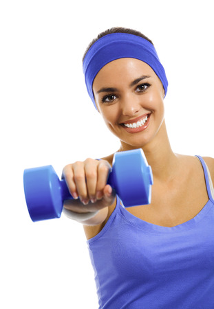 Happy smiling woman in violet sportswear, doing fitness exercise with dumbbell, isolated against white background. Young sporty dark-haired model at studio shot. Health, beauty and fitness concept. 免版税图像