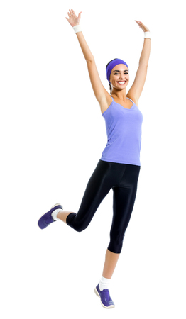 Full body of happy smiling woman jumping or doing fitness aerobics exercise, isolated against white background. Young sporty dark-haired model with raised up arms, in violet sportswear, at studio shot.