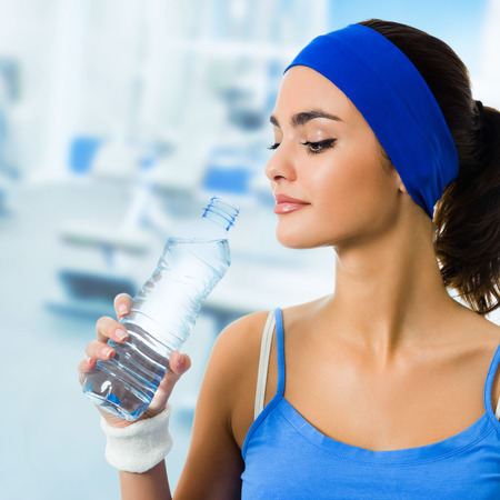 Portrait of smiling young beautiful woman in blue sport wear drinking water, at fitness club or center