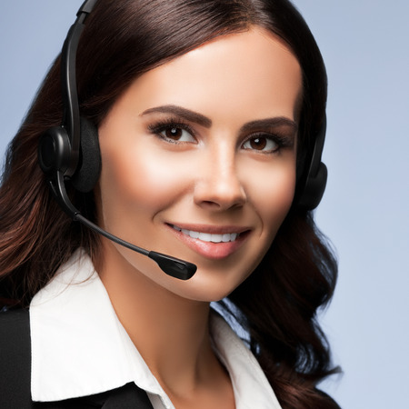 Portrait of cheerful customer support female phone operator in headset, over grey background. Consulting and assistance service call center.