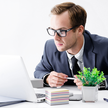 Serious businessman in glasses and black suit working with laptop computer at office. Success in business, job and education concept.
