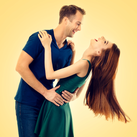 Portrait of hugging or dancing couple, looking at each other, with smile, over yellow background. Love, relationship, dating, flirting, lovers, romantic studio concept.
