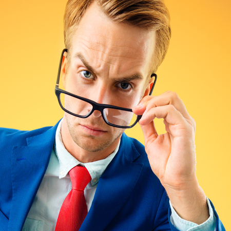 Are you seriously?! Portrait of funny skeptic businessman in blue confident suit and red tie, looking through glasses, over yellow-orange color background. Business concept.