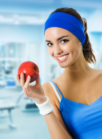 Portrait of young smiling woman in blue sportswear with red apple, at fitness club or center. Beauty and health concept. Imagens