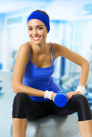 Young happy woman in blue sportswear doing exercise with pilates ball and dumbbell, at fitness club or center. Beauty and health concept.