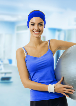 Young happy woman in blue sportswear with pilates ball, at fitness club or center. Beauty and health concept.