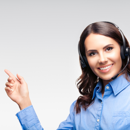 Portrait of call center customer support phone operator in headset pointing at something or showing copy space area for some text, advertising or slogan, over grey background