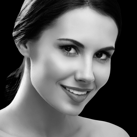 Portrait of beautiful smiling young woman with naked shoulders. Black and white. Stock fotó