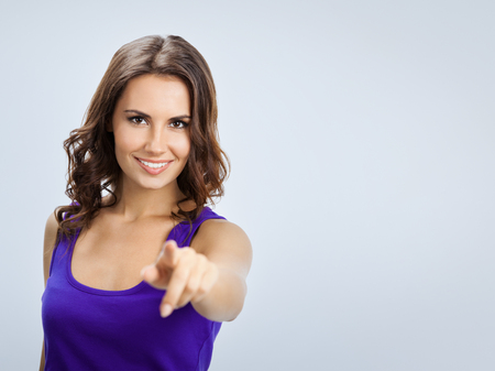 Portrait of happy smiling beautiful young woman in violet casual clothing, pointing at something over her finger or pressing virual button, over grey background, with blank copyspace area for slogan or text Stockfoto
