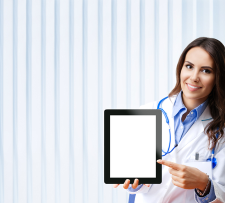 Portrait of happy smiling young female doctor showing no-name tablet pc with blank copyspace area for slogan or text, at office. 版權商用圖片