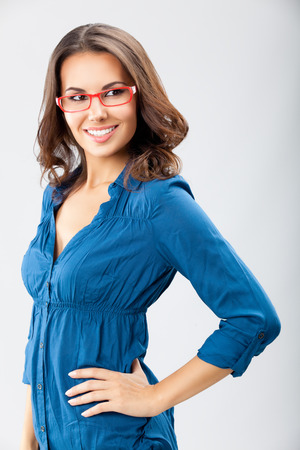 Portrait of happy smiling young cheerful businesswoman, in glasses, over grey background. Caucasian brunette model in business concept studio shoot.