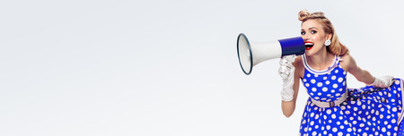 Portrait de femme tenant un mégaphone, vêtue d'une robe bleue de style pin-up à pois et gants blancs, avec un espace de copie vide pour du texte, de la publicité ou un slogan, sur fond gris Banque d'images