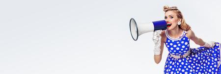 Retrato de mujer sosteniendo megáfono, vestida con un vestido azul estilo pin-up con lunares y guantes blancos, con espacio de copia vacía para algo de texto, publicidad o lema, sobre fondo gris Foto de archivo
