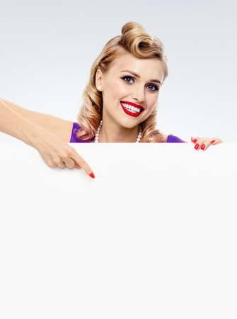 Woman in pin-up style dress, showing blank signboard with empty copy space place for some text, advertising or slogan, against grey background