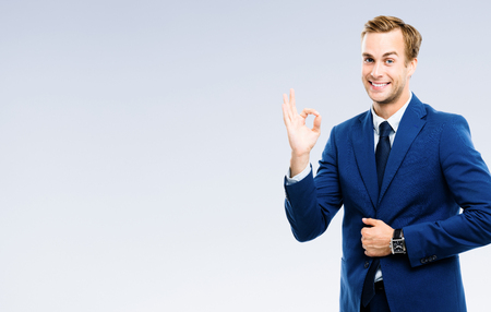 Bright image of happy gesturing young businessman, over grey background. Success in business, job and education concept studio shot.