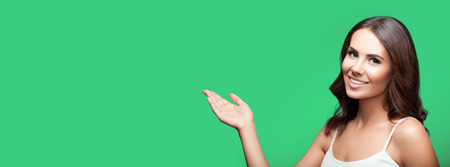 Young happy woman showing something, over green background 写真素材