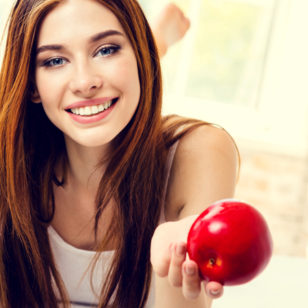 Picture of smiling woman with red apple, indoors. Beauty and dieting concept. Weight lossing, by healthy eating.