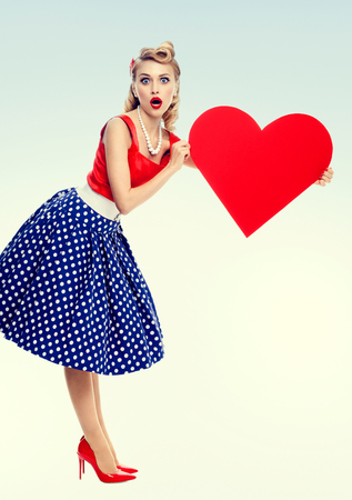 Bright photo of woman holding heart symbol, dressed in pin-up style dress with polka dot. Caucasian blond model posing in retro fashion and vintage concept studio shoot.