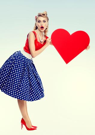 Foto luminosa della donna che tiene il simbolo del cuore, vestita con un abito stile pin-up a pois. Modello biondo caucasico in posa di moda retrò e riprese in studio concetto vintage.