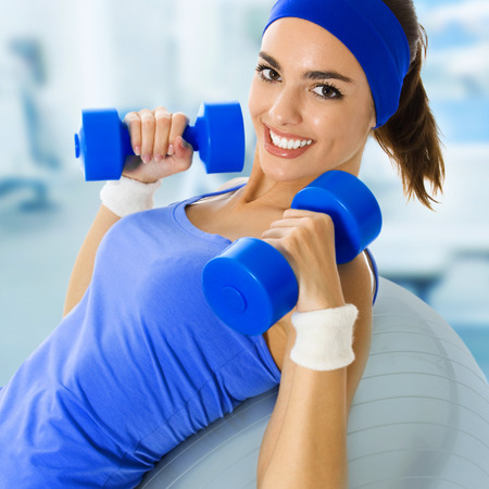 Young happy woman doing exercise, at fitness club or center Stock Photo