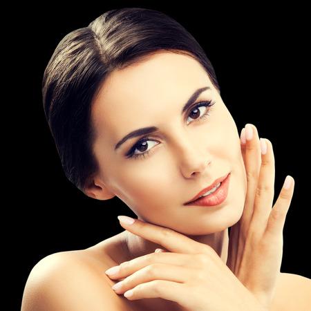 Porträt der schönen jungen Frau mit den Schultern, getrennt gegen schwarzen Hintergrund. Brünettes Modell - Schönheit, Glamour, Mode, Modellierung, Kosmetik, Gesundheitshaut und Körperpflegekonzept Studioaufnahme. Standard-Bild