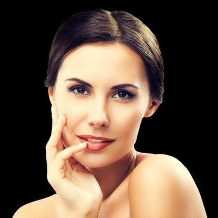 Portrait de la belle jeune femme aux épaules, isolée sur fond noir. Modèle brune - beauté, glamour, mode, modélisation, cosmétiques, concept de soins de la peau et du corps tourné en studio.