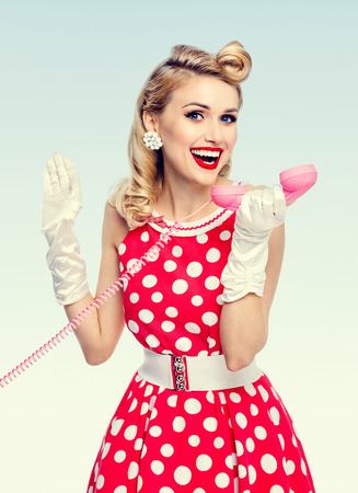 Bright photo of beautiful happy woman with phone, dressed in pin-up style red dress in polka dot and white gloves. Caucasian blond model posing in retro studio shoot.